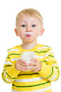 Funny kid drinking milk from glass or yoghurt Stock Photo
