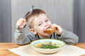 Funny kid with piece of bread and plate of soup Royalty Free Stock Photo