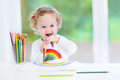 Funny laughing baby girl drawing at a white desk Royalty Free Stock Photo
