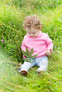 Funny laughing baby girl playing in a blooming garden little Stock Photography