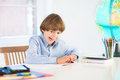 Funny laughing boy doing his homework at a white desk Royalty Free Stock Photos