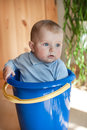 Funny little baby boy playing in blue bucket indoor Stock Images