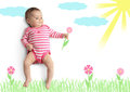 Funny little baby with drawn flower on meadow Royalty Free Stock Photo