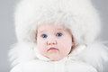 Funny little baby girl wearing a huge fur hat and white warm snow jacket ready for walk on cold winter day Royalty Free Stock Photo