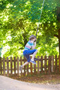Funny little boy enjoying swing ride on a playground beautiful summer day Stock Photography