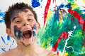 Funny little boy with paint splodges on his face artistic standing in front of completed modern abstract creation laughing at Stock Photos
