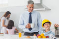 Funny little boy wearing fathers hardhat during breakfast while his mother and sister are cooking Stock Image