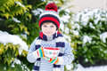 Funny little child holding big cup with snowflakes and hot chocolate drink and marshmallows Royalty Free Stock Photo
