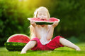 Funny little girl biting a slice of watermelon outdoors on warm and sunny summer day Royalty Free Stock Photo