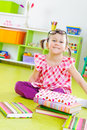 Funny little girl with books on floor Royalty Free Stock Photo