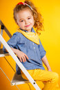 Funny little girl on a bright yellow background. Royalty Free Stock Photo