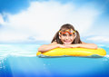 Funny little girl with diving glasses floating inflatable ring a