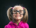 Funny little girl in funny big spectacles on grey Stock Photography