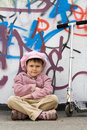 Funny little girl with scooter near graffiti wall Stock Image