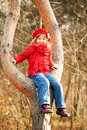 Funny little girl sitting on tree and smiling wearing a red in a Stock Photo
