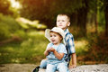 Funny little girl sitting with your brother in the Park Royalty Free Stock Photo