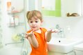 Funny little girl washing hands in bathroom Royalty Free Stock Photo