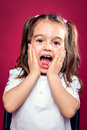 Funny little girl wit surprise expression over red background Royalty Free Stock Image