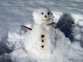 Funny little icey snowman silly in melting snow with leaf twig and pebble features in winter Stock Images