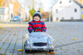 Funny little kid boy driving old car outdoors Royalty Free Stock Photo