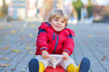 Funny little kid boy driving toy car outdoors Royalty Free Stock Photo