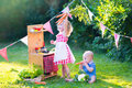 Funny little kids playing with toy kitchen in the garden curly girl and adorable baby boy cute brother and sister together a Royalty Free Stock Photo