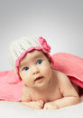 Funny little newborn baby wearing a hat with flower towel Stock Images