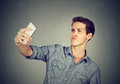 stock image of  Funny looking man taking pictures of himself with smartphone