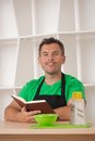 Funny man in apron cooking half length portrait of happy handsome playing fool the kitchen wearing and preparing to cook with book Stock Photos