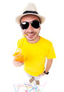 Funny man drinking juice wearing sun glasses hat and yellow t shirt on white background Royalty Free Stock Image