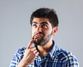 Funny man wondering young is while he pulling his lip downwards with finger isolated on grey Royalty Free Stock Photography
