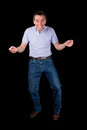 Funny middle age man dancing with cheesy grin black background Stock Images