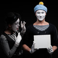 Funny mimes couple holding sign Stock Photos