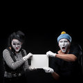 Funny mimes couple holding sign Royalty Free Stock Image
