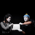 Funny mimes couple holding sign Stock Photography