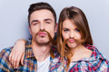 Funny moustache beautiful young loving couple making fake from hair while standing against grey background Royalty Free Stock Image