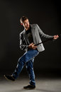 Funny negligent young man with walking stick on dark studio background Stock Photos