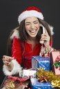 Funny phone call on christmas cheerful young woman dressed in santa outfit laughing during a conversation against dark background Stock Photography