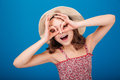 Funny playful little girl in hat making glasses by hands Royalty Free Stock Photo