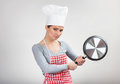 Funny portrait of a woman with the pan in chef s hat in her hands on gray background Stock Photos