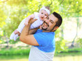 Funny positive father and baby having fun outdoors in summer Royalty Free Stock Photo