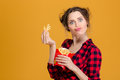 Funny pretty young woman making fake moustache with fries in checkered shirt over yellow background Royalty Free Stock Images