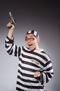 Funny prisoner with firearm on gray