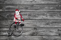 Funny red santa claus on wooden grey background in hurry for buy buying christmas presents sitting a old bike Royalty Free Stock Photo