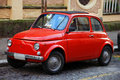 Funny red small old little italian car with round headlights and Royalty Free Stock Photo