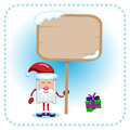 Funny santa claus and table holds a under a in a gift lies snow Royalty Free Stock Photo