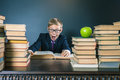 Funny school boy reading a book at library. Joke! Royalty Free Stock Photo