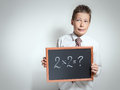 Funny schoolboy has thought of the task decision cute teenager in a white shirt thinking about on black chalkboard and do not know Stock Image