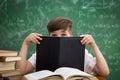 Funny schoolboy hiding behind book Royalty Free Stock Photo