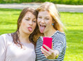 Funny selfie cheeky girlfriends with smartphone in park Stock Photos